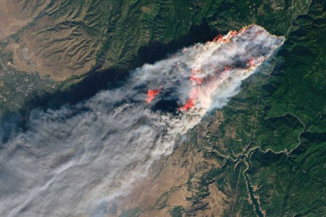 Satellite image of a section of california, showing angry red fire and smoke streaming across a strip of green land