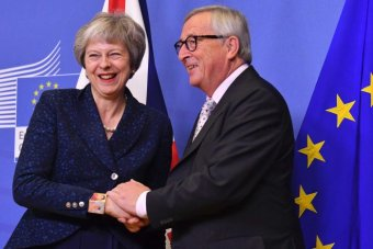 A smiling Theresa May and Jean-Claude Juncker shake hands
