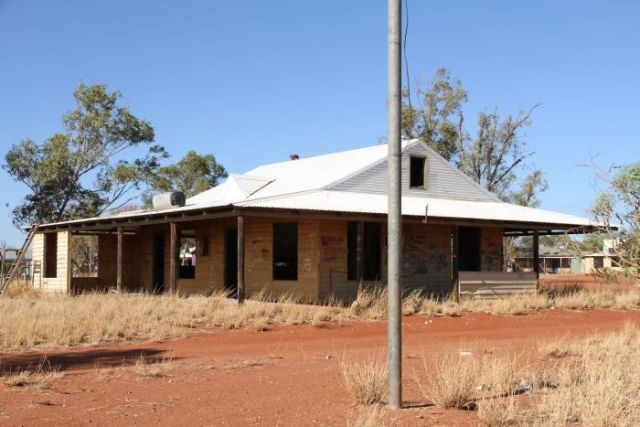 a dilapidated house falling apart in a dry, outback setting