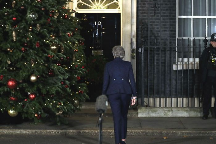 Theresa May walks away from a microphone outside 10 Downing Street, towards the door. There is a large Christmas tree next her.