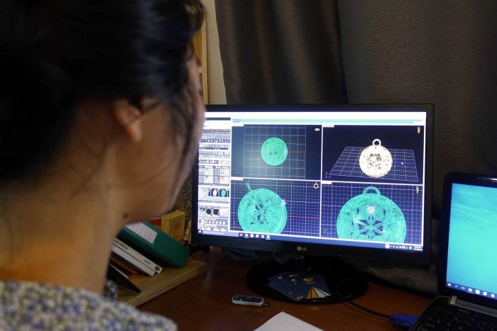 Mana Ohori looks at a computer generation of a pendant.