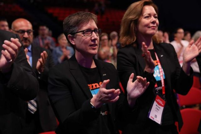 Sally McManus applauds in front of a crowd