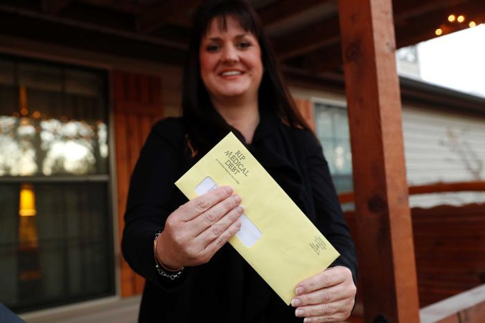 A woman holds a bright yellow envelope that confirms that her medical debt has been erased on her house's front verandah.