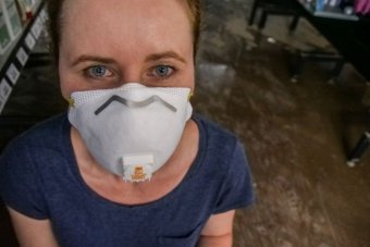 A woman wearing a face mask looking directly into the camera. Behind her is a water-covered floor.