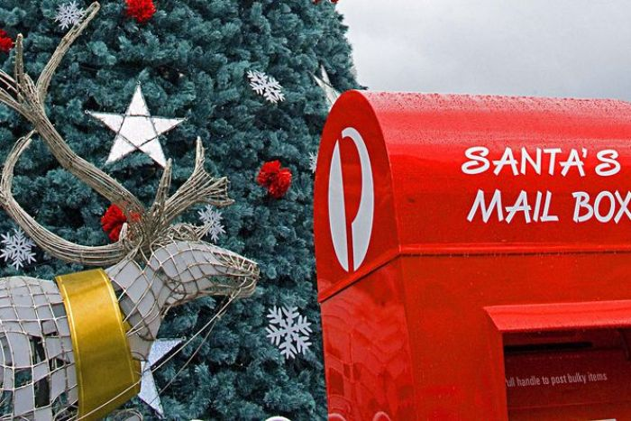 An Australia Post mail box next to a reindeer and Christmas tree