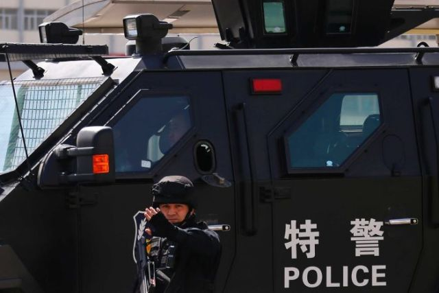 A Chinese police officer stands in front of an armoured police vehicle.
