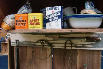 Old tins of Keen's Curry Powder, Keen's Mustard and bi-carb soda on a self in an old hut