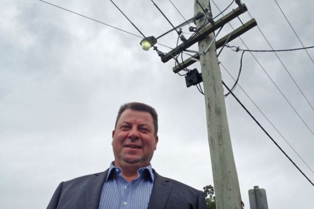 Energy consultant Marc White standing in front of a power pole supporting overhead electricity wires.