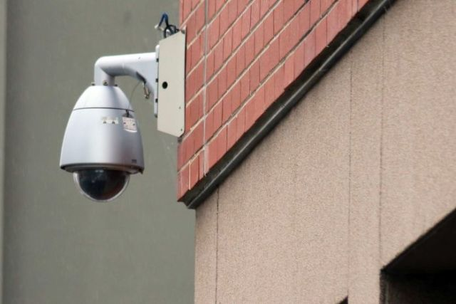 A security camera mounted to the side of a building in hobart.