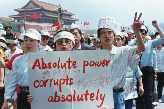 "A group of Chinese journalists hold a sign that says ""Absolute power corrupts absolutely"" and wear hats made out of newspapers."
