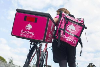 A Foodora delivery worker carries a bag of food and wheels a bicycle.