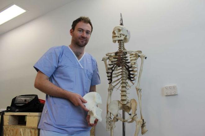 Orthopaedic surgeon Dr Jonathan Davis holds a 3D printed pelvis bone next to a human skeleton.