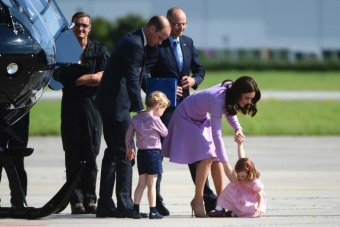 The Duchess of Cambridge attempts to help Princess Charlotte off the tarmac and back onto her feet.