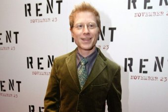 Actor Anthony Rapp wears an olive green suit and stands on the red carpet at the Rent premiere.