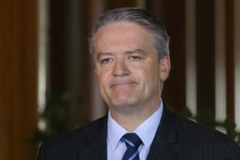 Mathias Cormann looks off to the left of frame, his mouth is frowning and he's wearing a navy pinstripe suit.