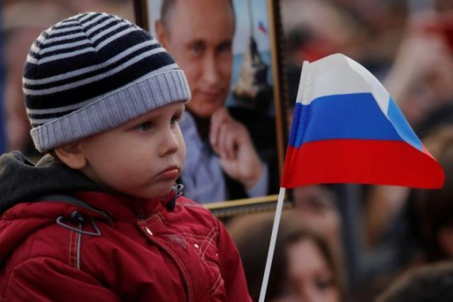 Young child waves a Russian flag