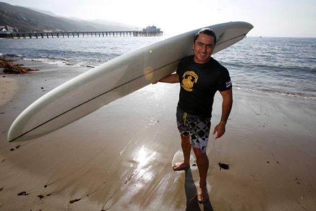 Ross Clarke-Jones stands on the beach holding his surfboard.
