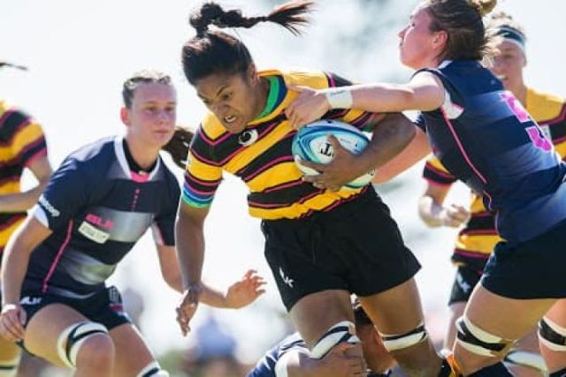 Wide shot of a female rugby player breaking a tackle.