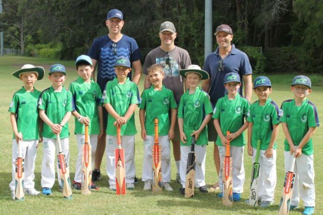 Team photo of young boys in cricket gear with their dads