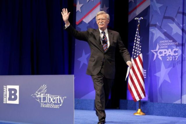 A man in a dark suit waves to a crowd while walking towards a lectern.