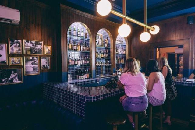 Three women sit at the bar of a new gastropub in Adelaide called Hotel Longtime.