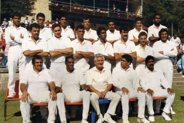 Aboriginal cricketers of 1988 pose on the pitch for a group photo with then-Prime Minister Bob Hawke.