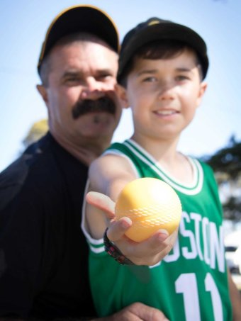 Laurie Marks and his young son Byron, against a brilliant blue sky. Byron holds a bright yellow cricket ball towards the lens.