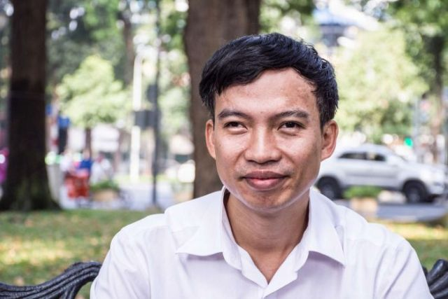Portrait of Tran Van Giap on a park bench