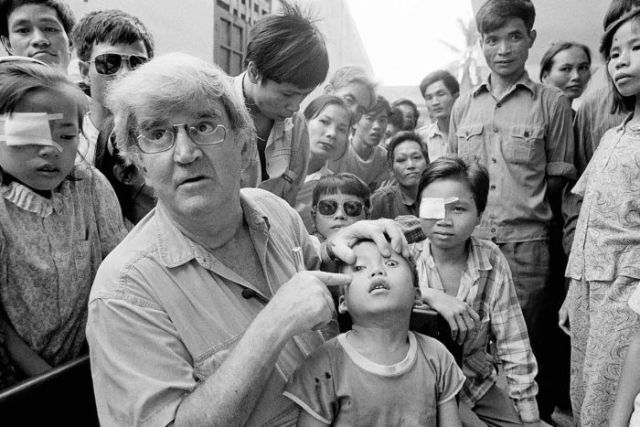 Dr Hollows points to a young boy's eye while a crowd of onlookers stare