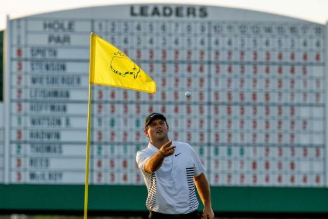 Golfer Patrick Reed catching a ball while the large leaderboard is in the background