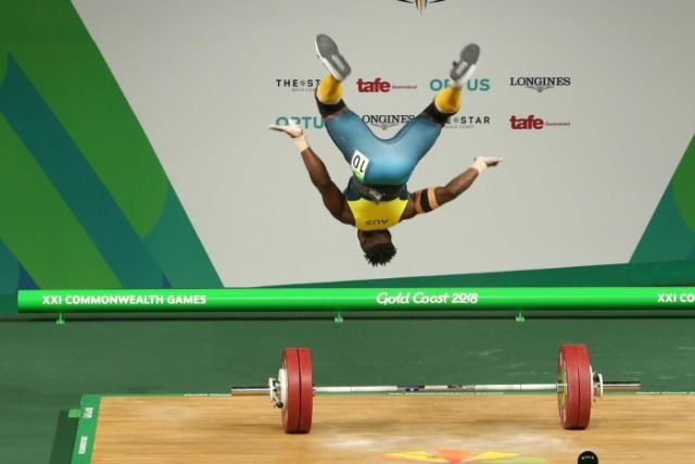 Australian weightlifter backflips after completing a successful snatch.