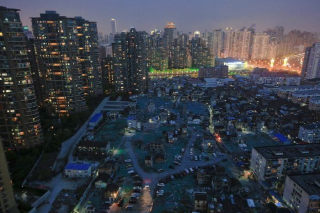 A night view of old houses surrounded by dozens of high-rise apartment buildings