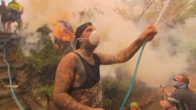 Locals defend a house in Menai from bushfire