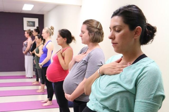 Pregnant women standing in a line practicing YogaBaby.