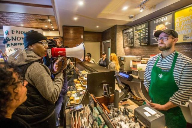 Black Lives Matter activist Asa Khalif yells at a Starbucks employee with a megaphone.