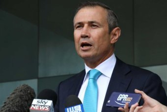 A picture of Roger Cook in blue tie speaking into microphones outside the ABC Perth office.