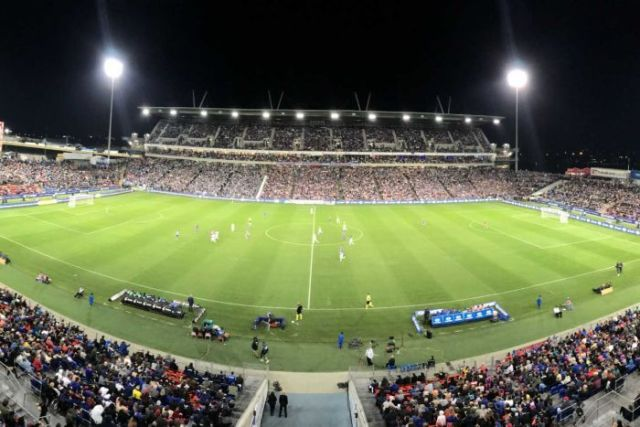 A wide image of a soccer stadium with filled stands.
