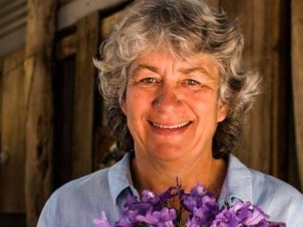 Suspected murder victim Cynda Miles from Margaret River holds a bunch of purple flowers.