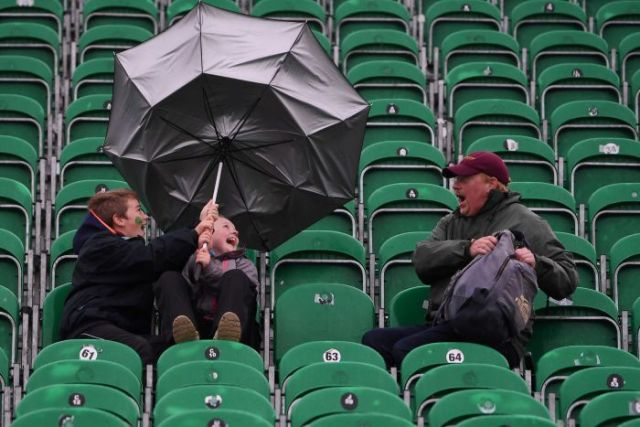 Two boys laugh as their umbrella flips with a shocked man looking on.