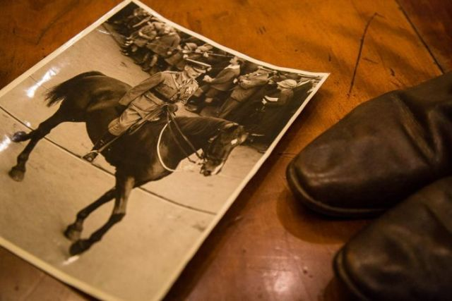 A photograph of Walter Cass leading the funeral procession for Sir John Monash sits on a table with a pair of  boots.