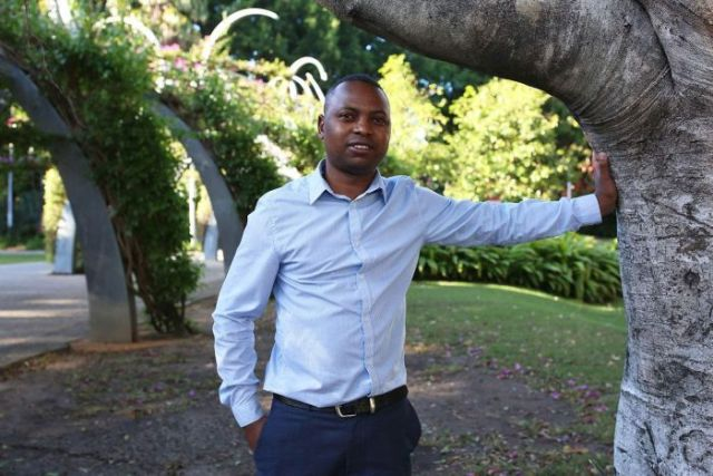 Tawanda Karasa stands next to a tree in a park in Brisbane on May 16, 2018.