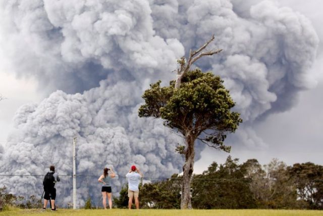 People watch as ash erupts from the Halemaumau crater near the community of Volcano.