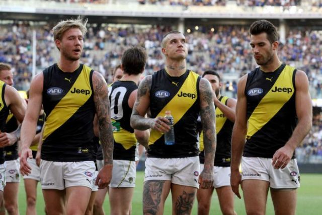 Dustin Martin (C) of the Tigers and teammates leave the field after a loss to West Coast in Perth.