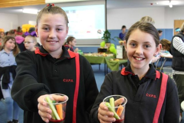 Two young girls holding cups of carrot and celery