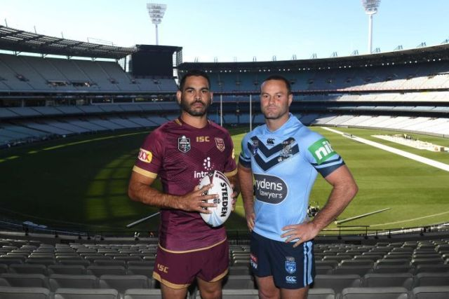 Greg Inglis holding a ball wearing a Maroons kit stands next to Boyd Cordner in a Blues kit with the MCG in the background.