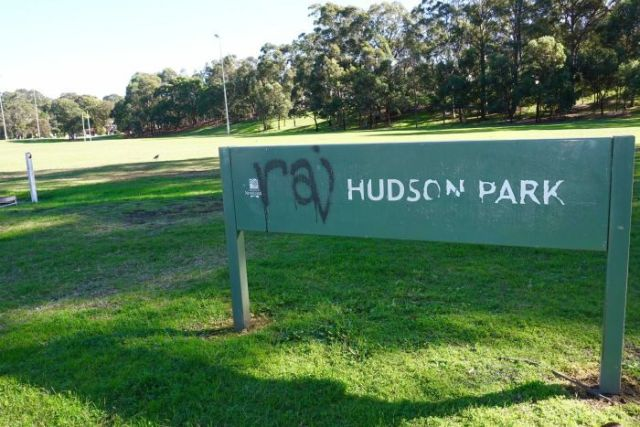 A graffitied green Hudson Park sign in front of park