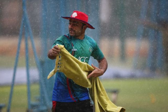 Afghanistan cricketer Rashid Khan runs for shelter during sudden rains at a training session.