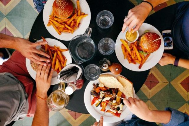 Four friends having burgers and beers at the pub.