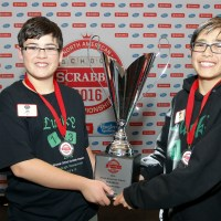 Jem Burch, left, and Cooper Komatsu from Los Angeles,  pose with the ChampionÕs trophy after defeating more than 160 teams at the 2016 North American School SCRABBLE Championship, at Gillette Stadium in Foxborough, Mass., Sunday, April 10, 2016. Burch and Komatsu won by 10 points with a final score of 411 to 401. (Stew Milne/AP Images for Hasbro)