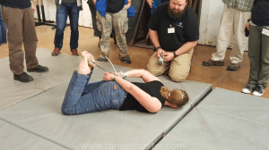 Caleb Causey from Lone Star medics coaching Julie Thomas through the friction cutting process in case your hands are zip tied behind the back. Photo from Tiffany Johnson.